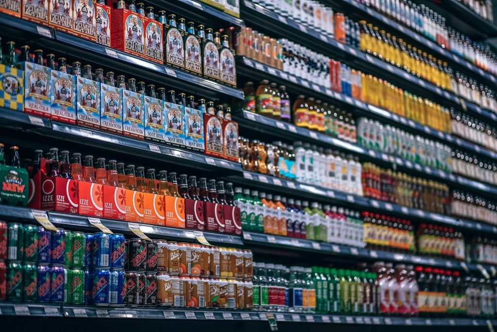 Grocery store isle filled with different sodas and fruit juices.