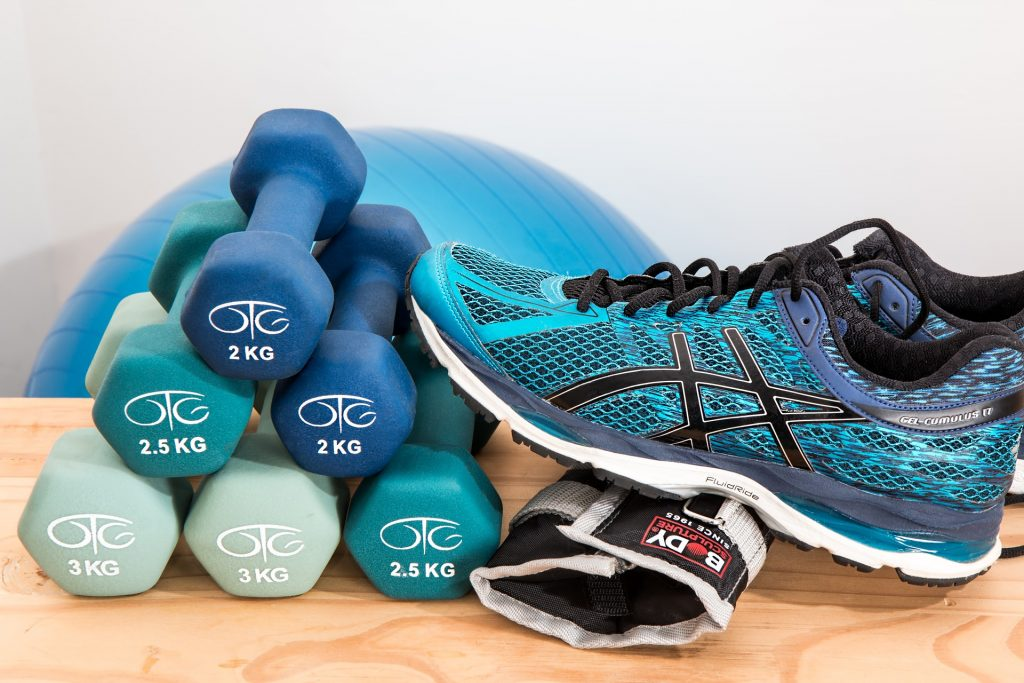 Different colored small weights on table, next to running shoe and stability ball.