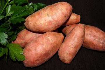 Whole sweet potatoes stacked on each other with parsley on the side.