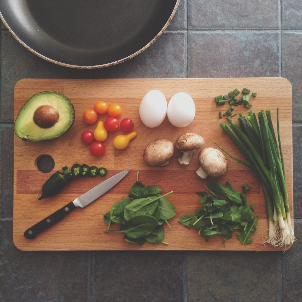 Wood cutting board with avocado, jalapeno, tomatoes, spinach, arugula, eggs, mushrooms and scallions.