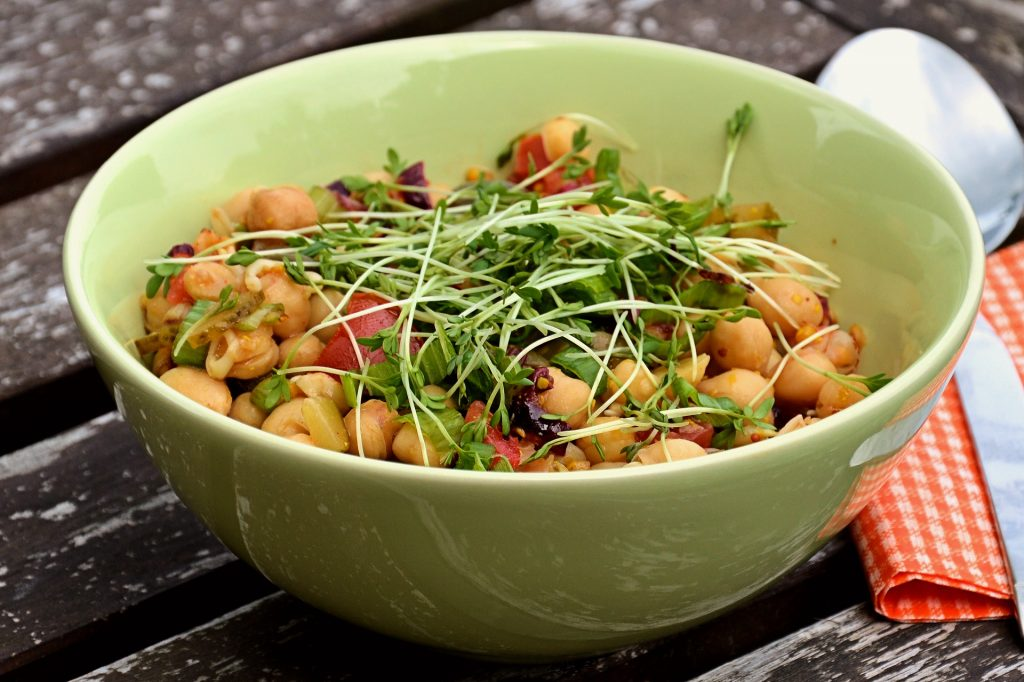 Salad with chickpeas and finely chopped vegetables. Garnished with herbs.