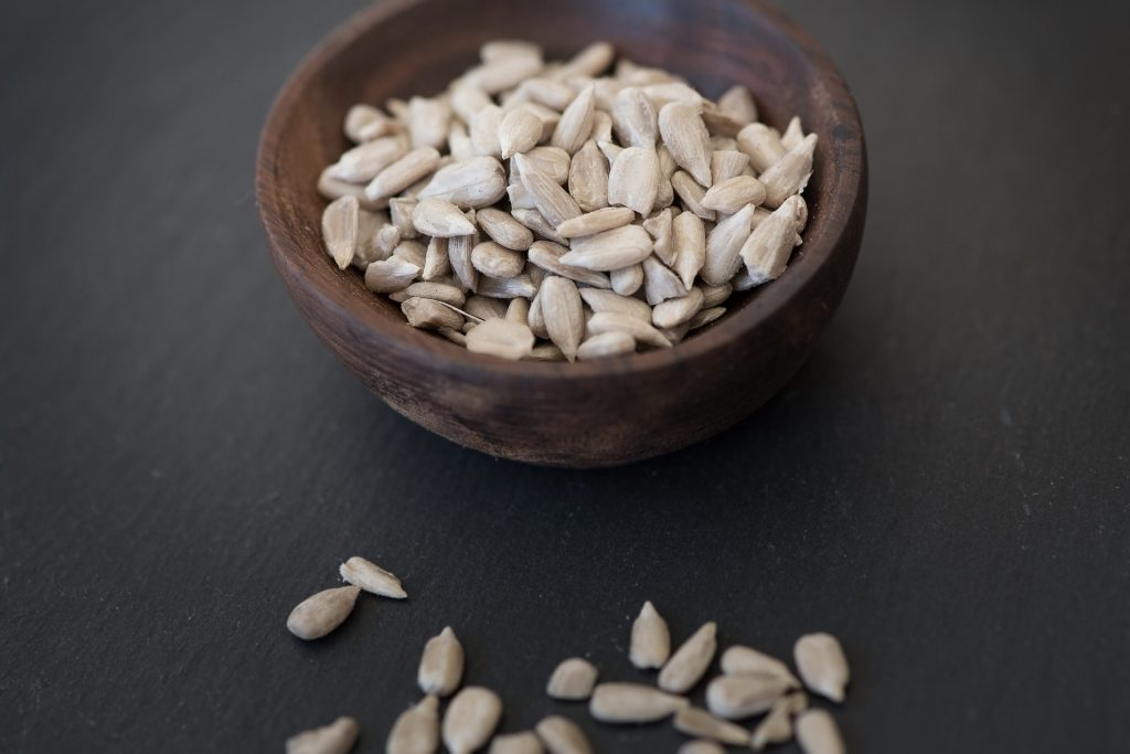 Sun flower seeds in small wooden bowl.