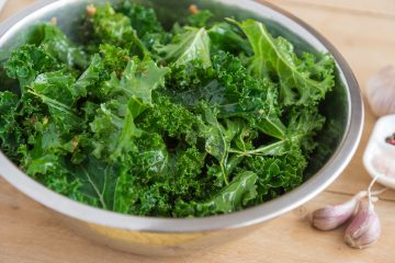 Chopped kale in bowl with dressing and seasonings.