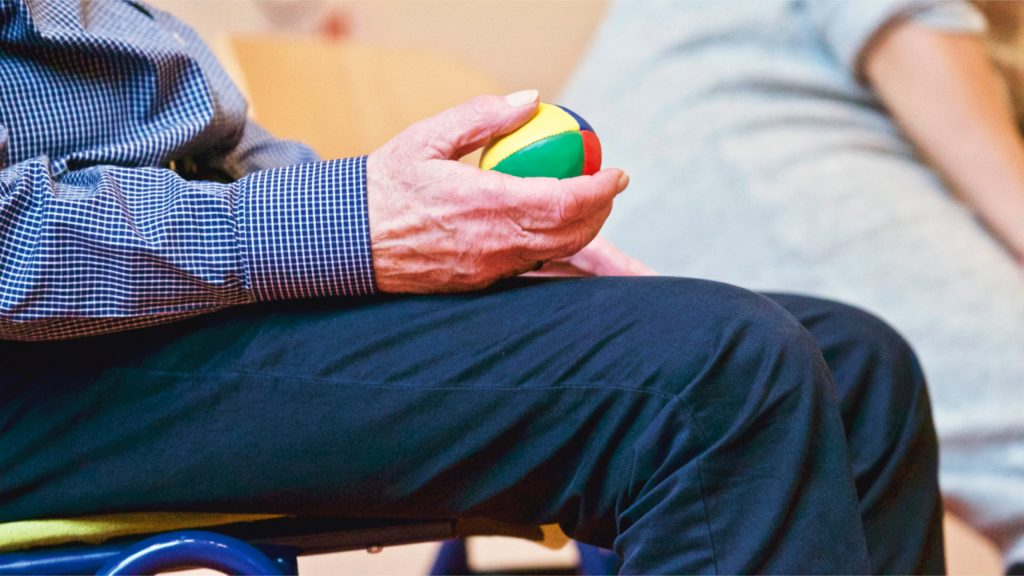 Older man sitting while holding a small ball.
