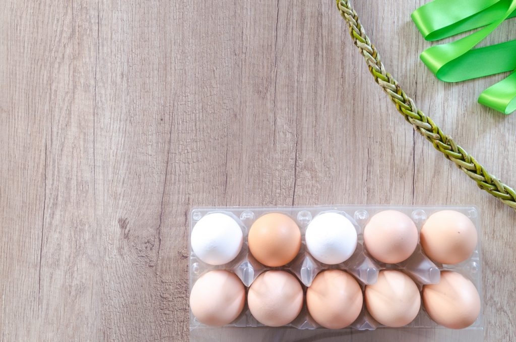 Plastic carton of eggs, colored brown and white, on wood surface.
