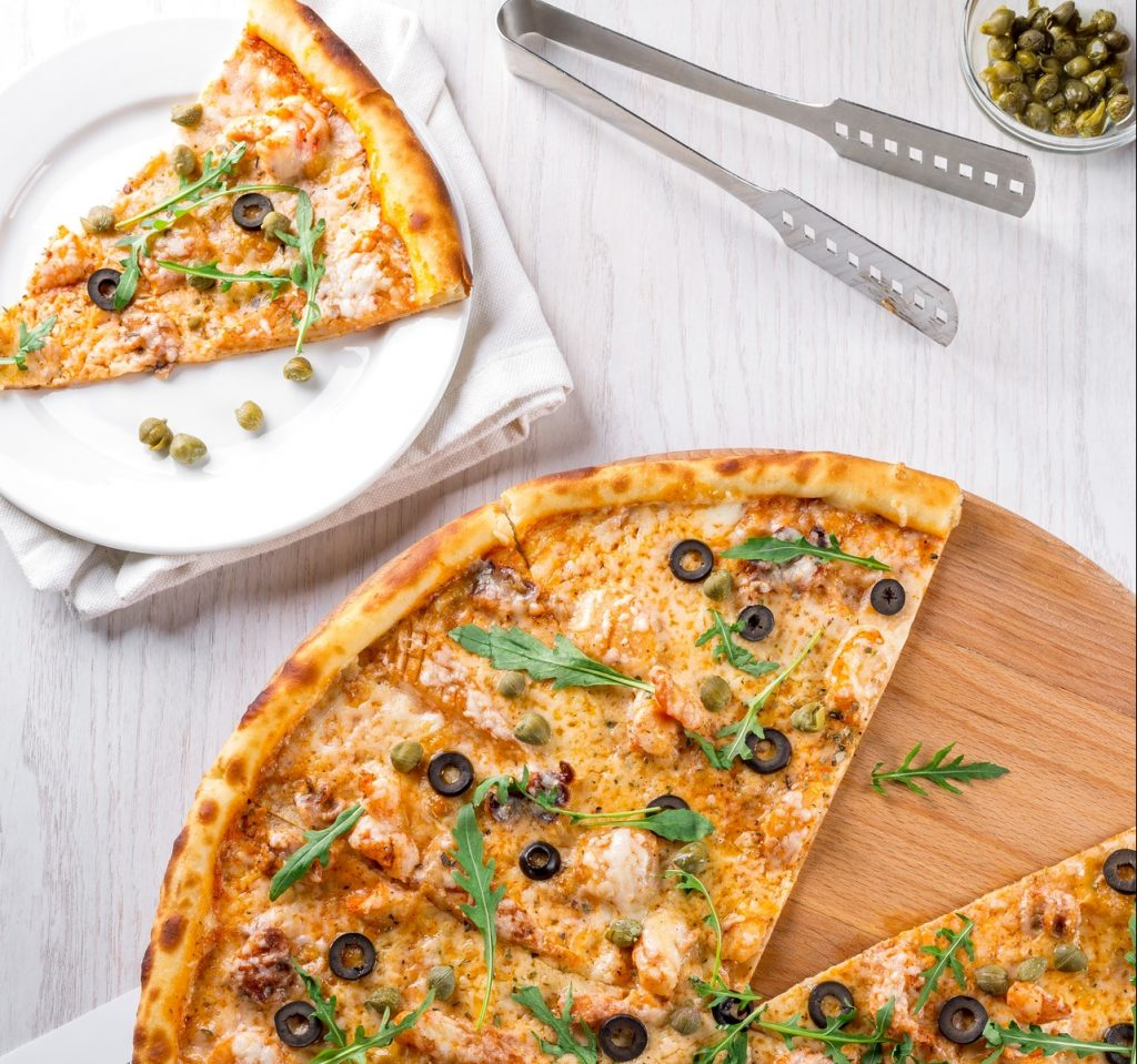 Pizza topped with olives, capers, chicken and arugula. One piece of pizza is placed on a small plate.