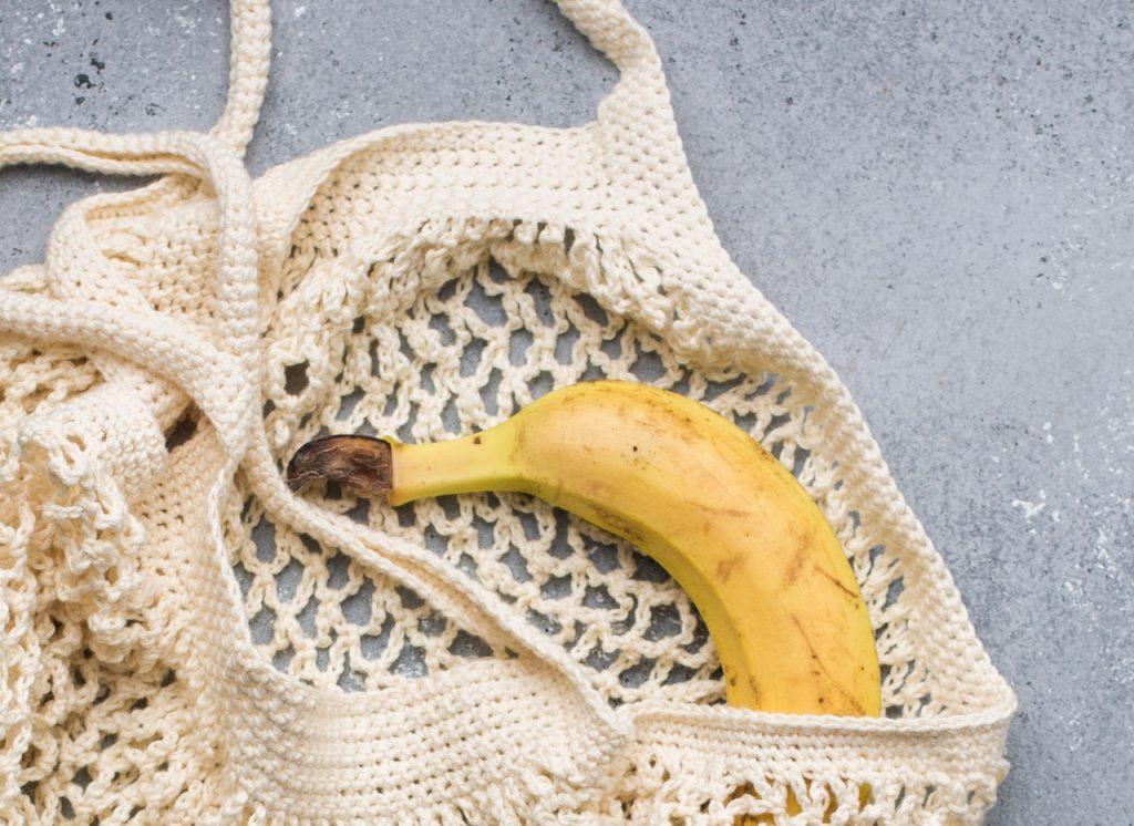 Banana in knit reusable shopping bag.