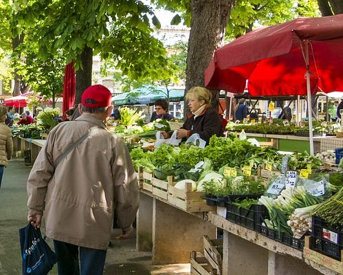 Outdoor farmer's market with customers strolling down isle of produce.