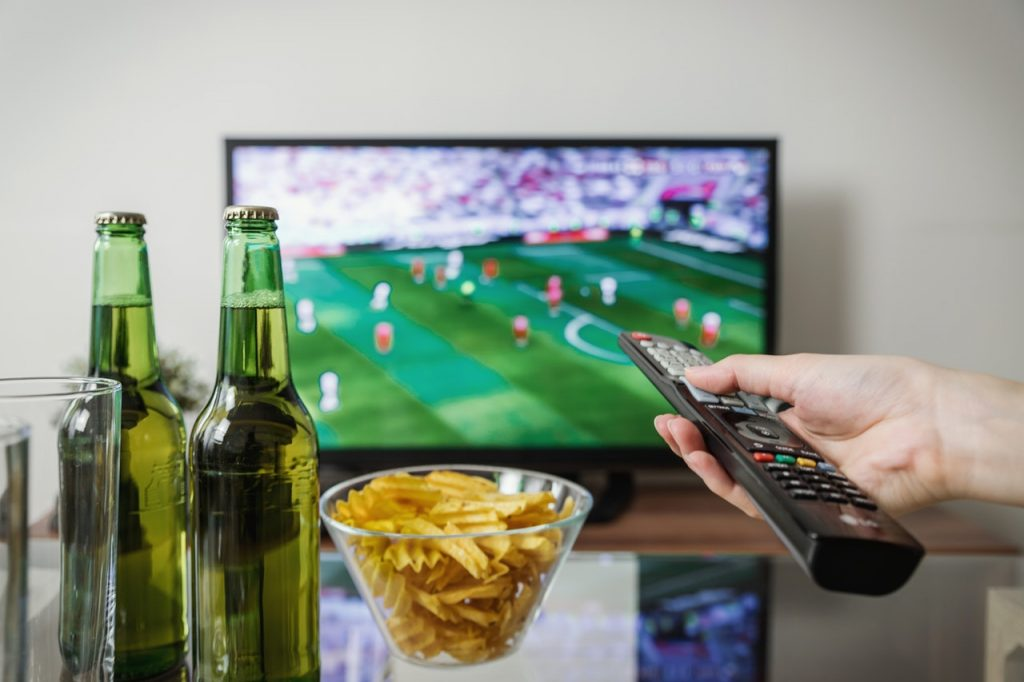 Person pointing remote at TV with soccer game on. Beer and potato chips are visible on a table.