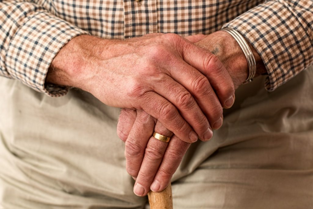 Man holding hands on top of cane.