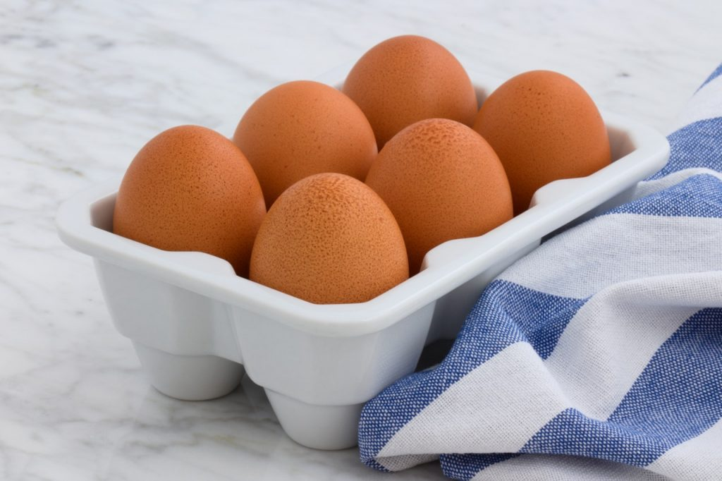 Carton of six brown eggs on white counter top with blue and white dishtowel.