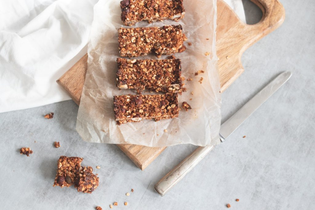 Homemade granola bars, freshly cut on top of parchment paper and a cutting board.