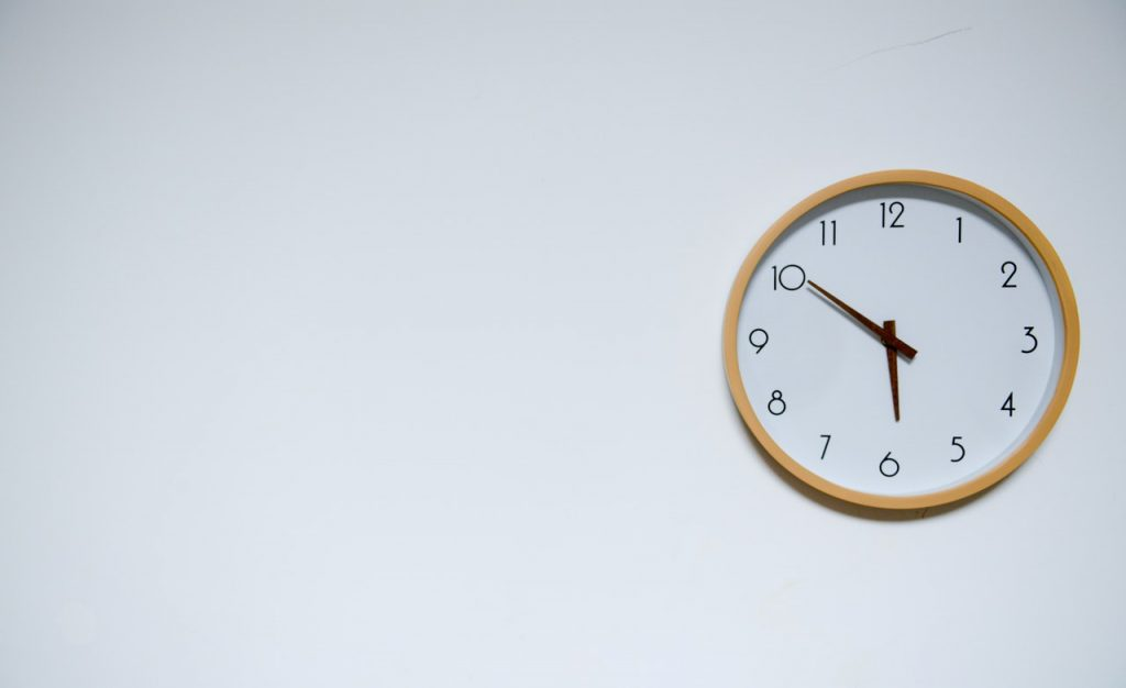 Wooden clock on white wall.