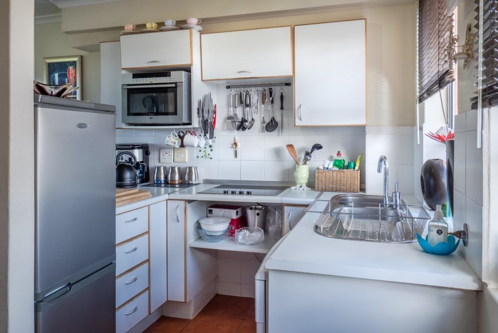 Home kitchen with white cabinets and counter tops, stainless steel sink, utensils and small appliances visible.