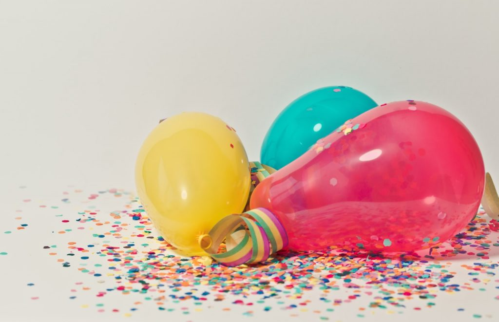 Variety of balloons surrounded by colored confetti.