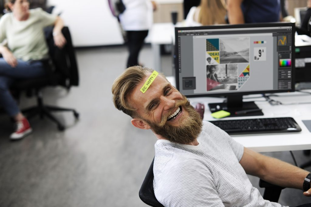 "Man smiling at desk with computer-- with a sticky note reading ""be happy!"" on forehead."