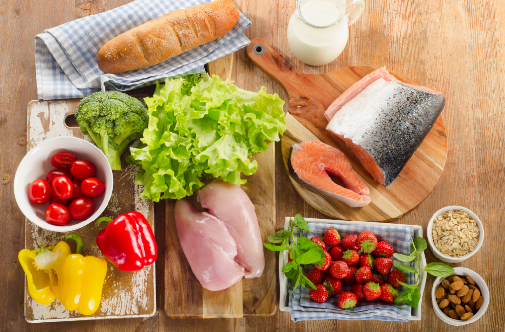 Iron rich foods on cutting boards, including salmon, chicken, broccoli, leafy greens, nuts and strawberries.