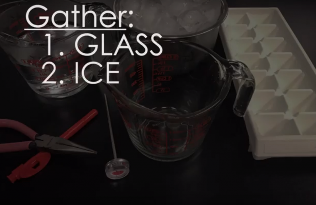 Screenshot from the video: Calbrating a Thermometer. There is a measuring cup, thermometer, water and ice on the table. The text on the picture reads: Gather: 1) Glass 2) Ice.