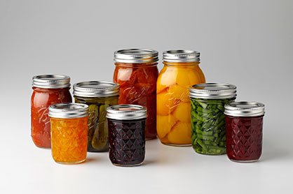 Assortment of canned fruits, vegetables and jams on a counter.