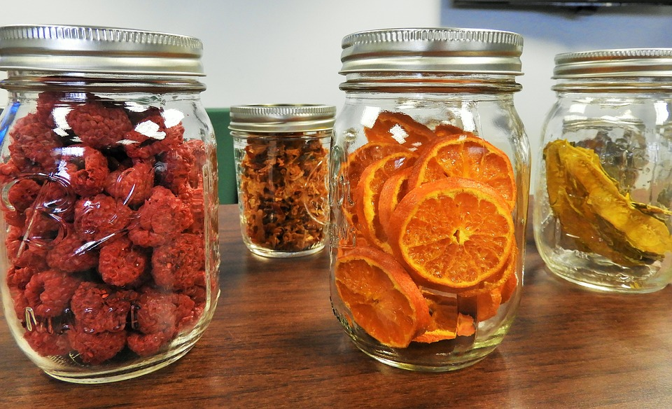 Dried fruits in small jars, including dried raspberries, dried oranges, and dried mango.