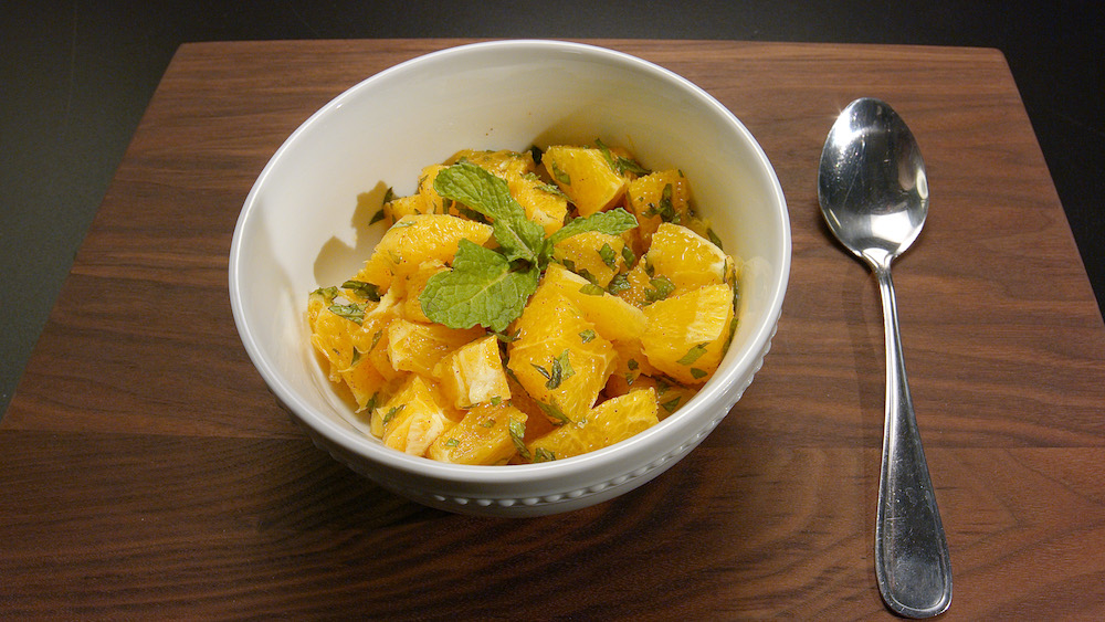 Bowl of cinnamon oranges, topped with mint.