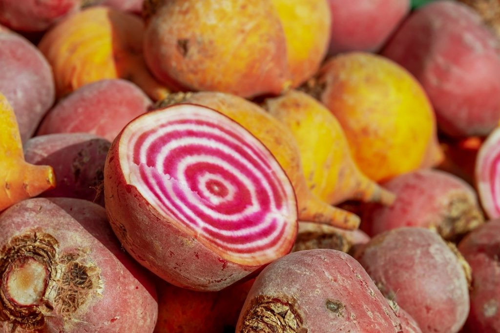 Cut raw beet in a pile of beets. The pink and white rings inside are visible.