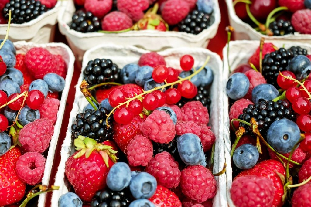 Mixed berries, including strawberries, black berries, raspberries and blueberries in a small carton.