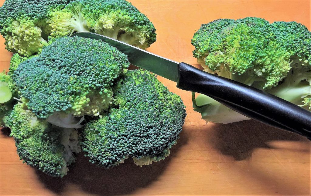 Raw broccoli on cutting board with knife.