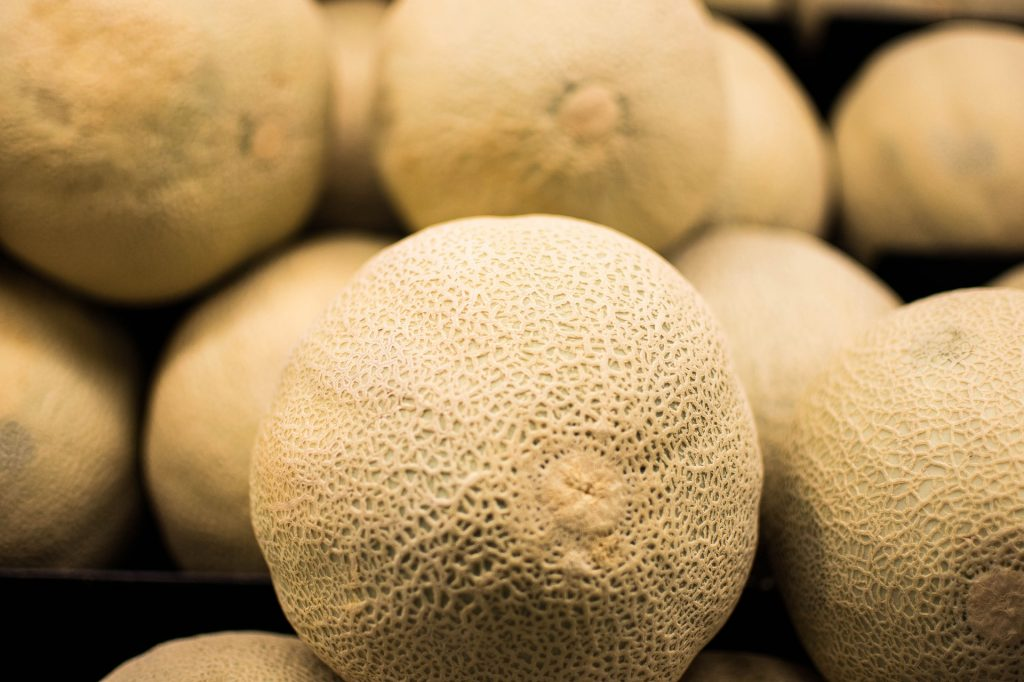 Raw, whole cantaloupe stacked on top of each other.