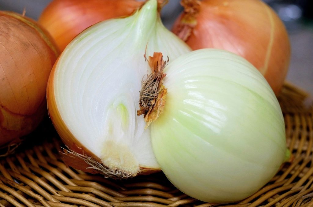 Whole white onion sliced in half on basket.