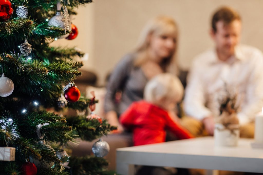 Father, mother and son sit at table in background of picture. Christmas tree with ornaments is the foreground of the image.