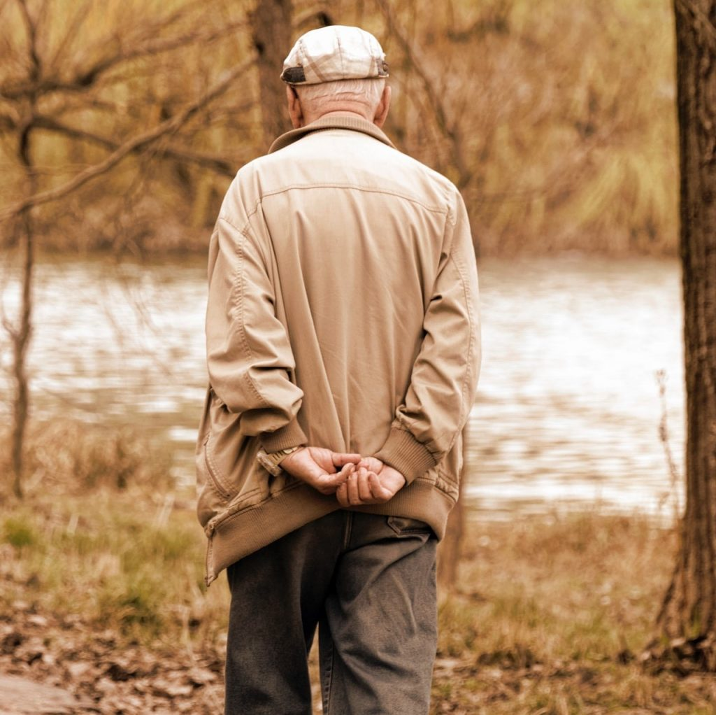 Older man walking outside with jacket on in the fall.