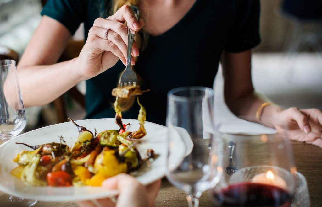 Woman taking bite of grilled vegetables, at table with wine, and candle.