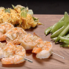 Grilled shrimp on cutting board with chickpea puree, sugar snap peas and cut lemon wedge.