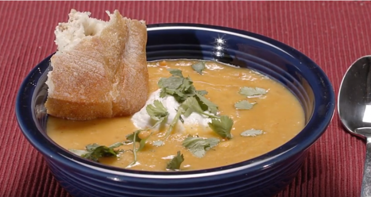 Red lentil soup with lemmon in a bowl, topped with coconut cream and a piece of bread.