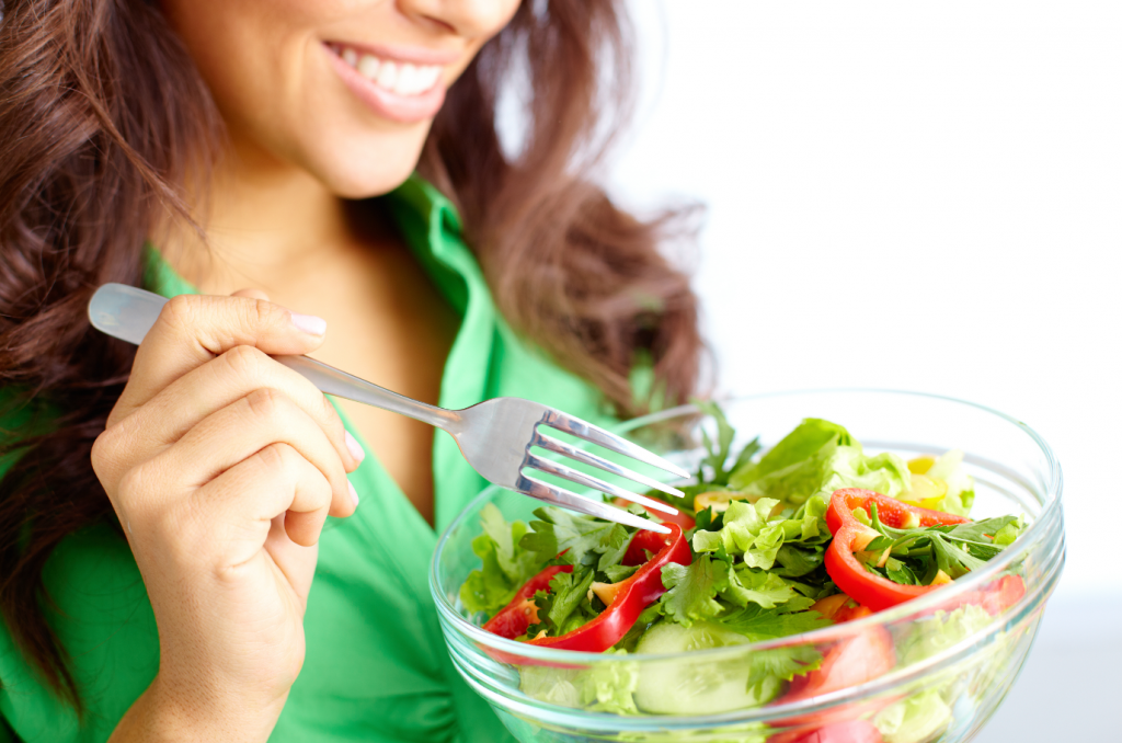 Woman smiling, looking down on salad she is eating with a fork.