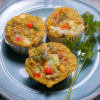 Individual egg frittatas on a plate, garnished with fresh parsley.