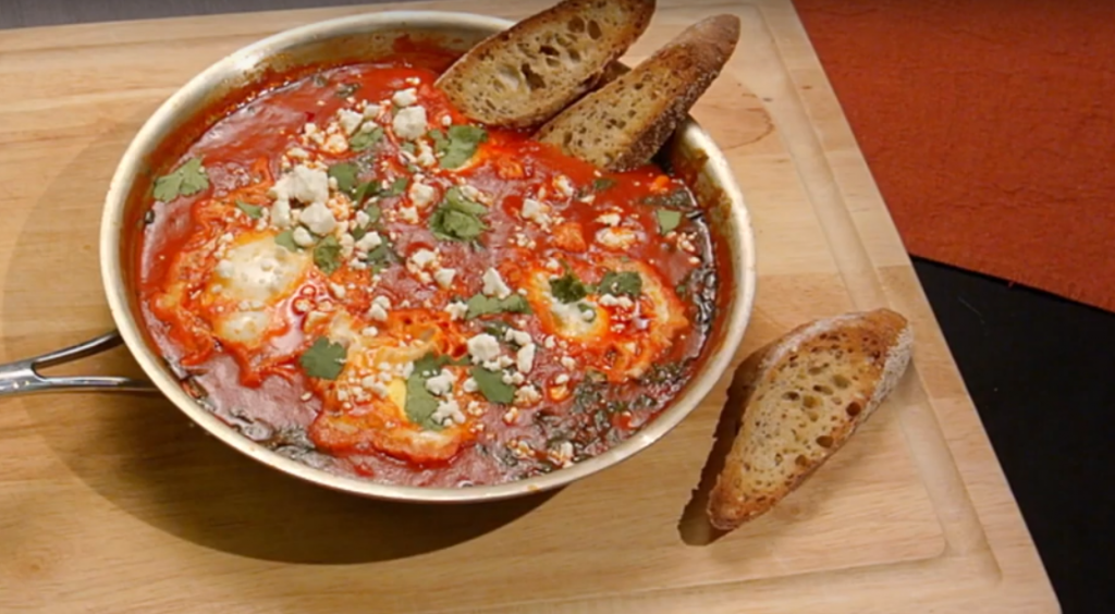 Shakshuka in pan with crusty bread on the side, topped with feta cheese and cilantro.