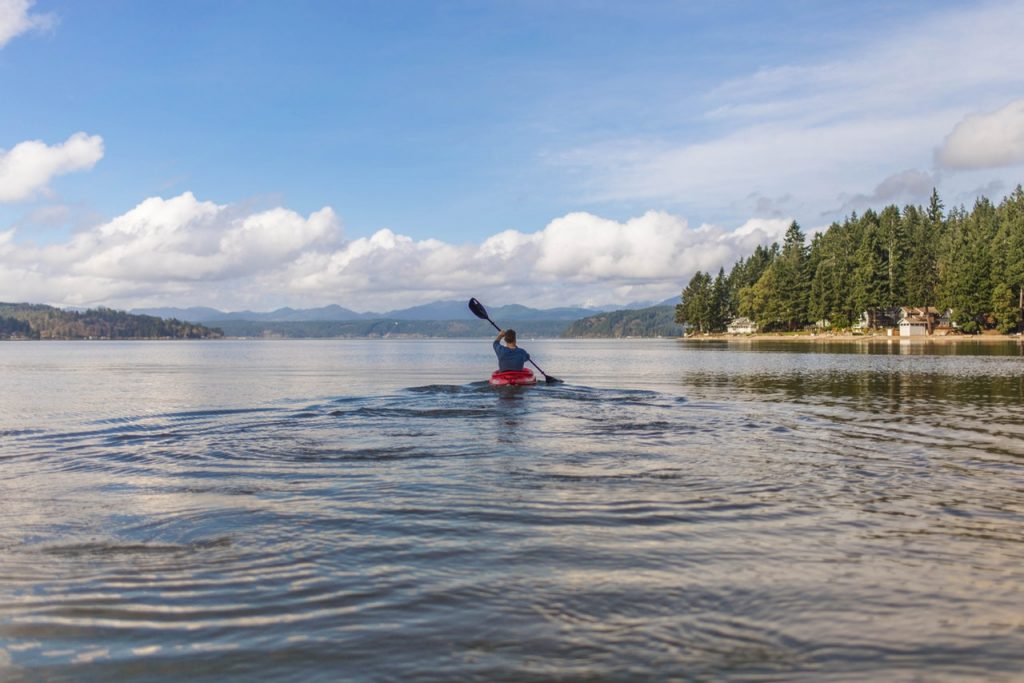 Man kayaking by himself outdoors on like with mountains and pine trees visible.