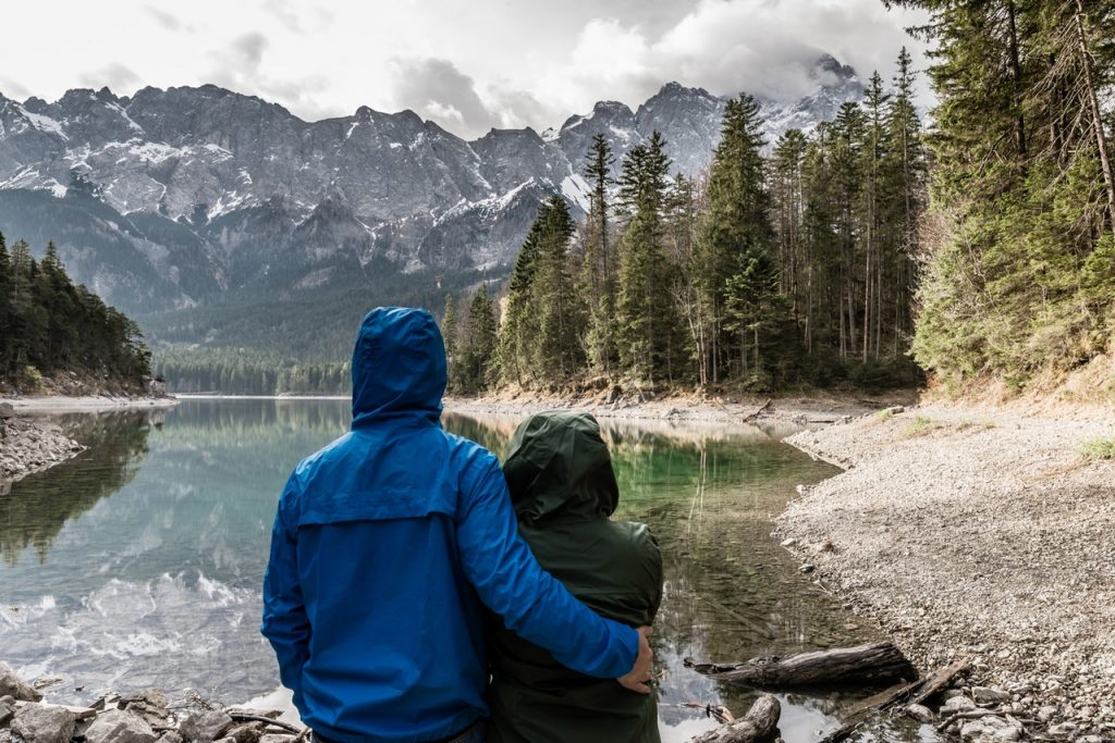 Man and woman sitting at lake, wearing hiking clothing, looking at the mountains.