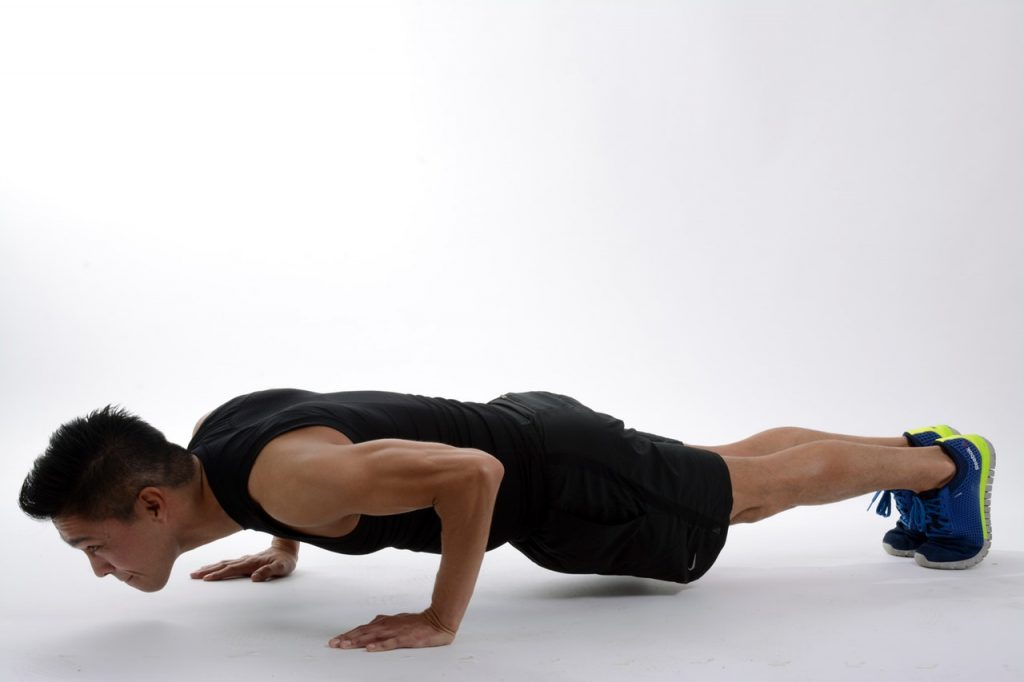 Man in a plank position on the ground.