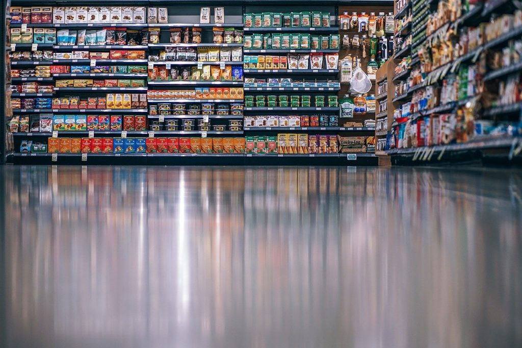 Grocery store isle, dried goods and canned goods on shelves are visible.