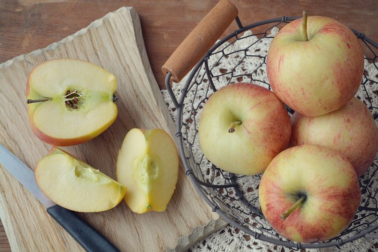 Bowl of whole apples beside small cutting board with cut apples.