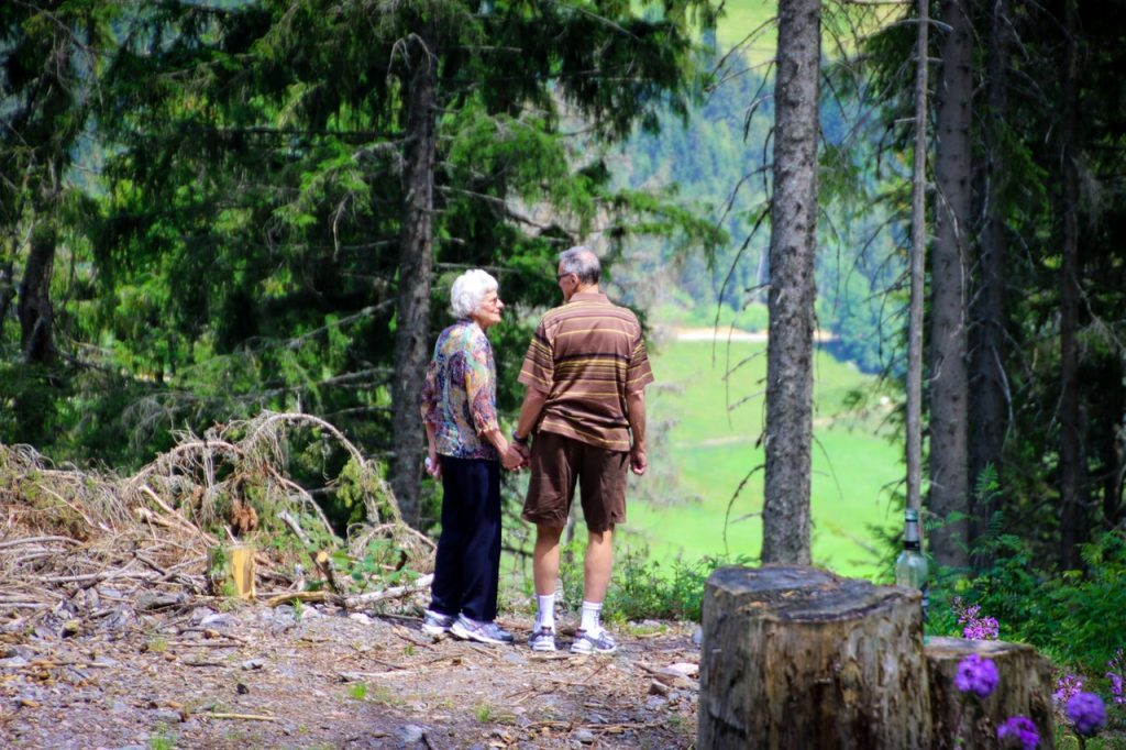Older man and woman hiking outside together, holding hands.