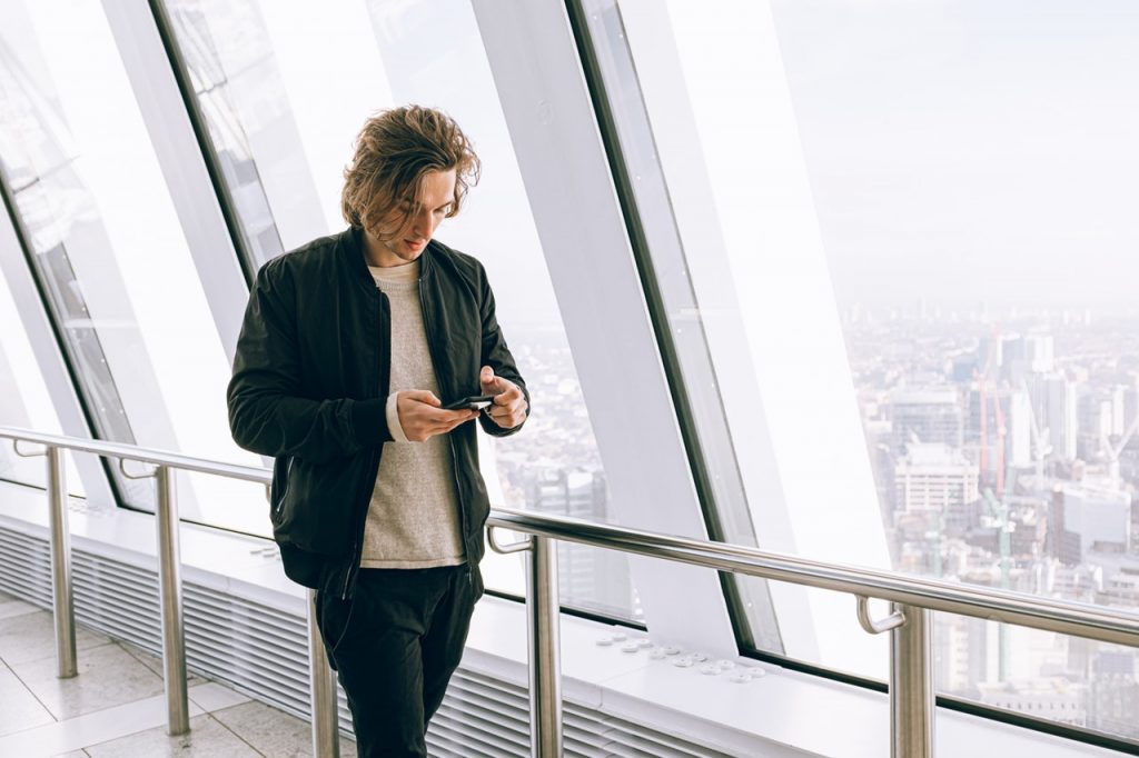 Man walking looking at phone wearing casual business clothing.