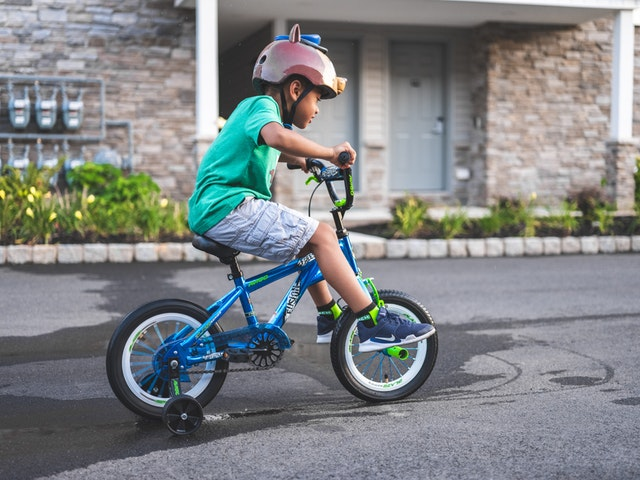 Small boy riding bike with training wheels, wearing helmet.