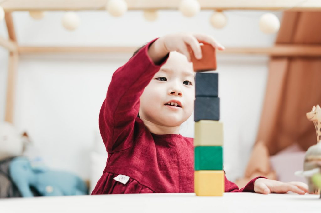 Young toddler playing with blocks, building tower.