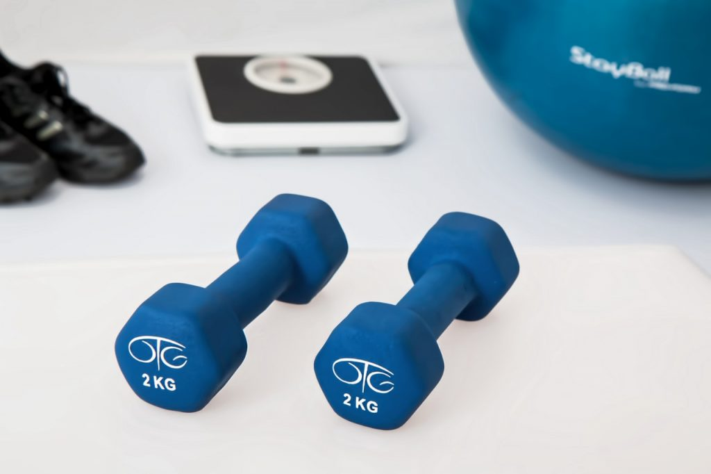 Two blue 2kg weights on table in front of scale, tennis shoes and stability ball.