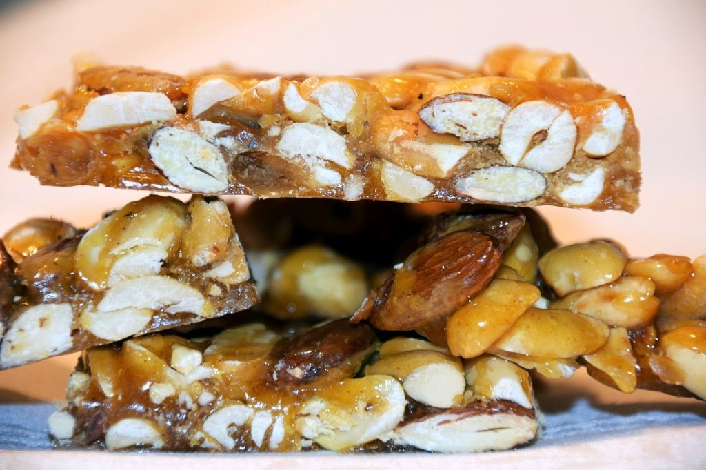 Nut brittle stacked on top of each other. Brittle uses peanuts, almonds, hazelnuts.
