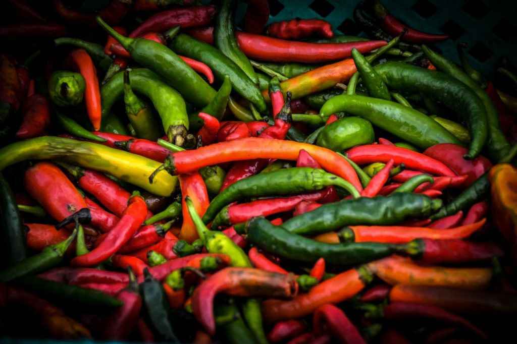 Green and red Chile peppers in a pile.